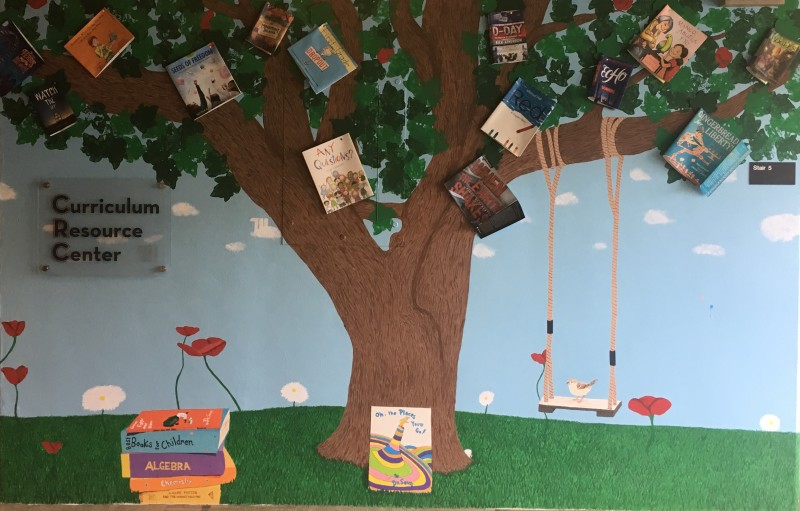 CRC Mural: depicts a tree in a field. There are book covers scattered among the leaves. There is a swing hanging from a branch, and a bird perched on the swing. A stack of books sits next to the tree, and a frog sits atop the books.