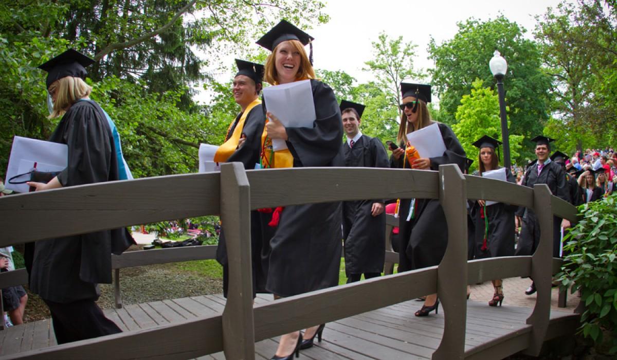 Graduate walking across Kissing Bridge