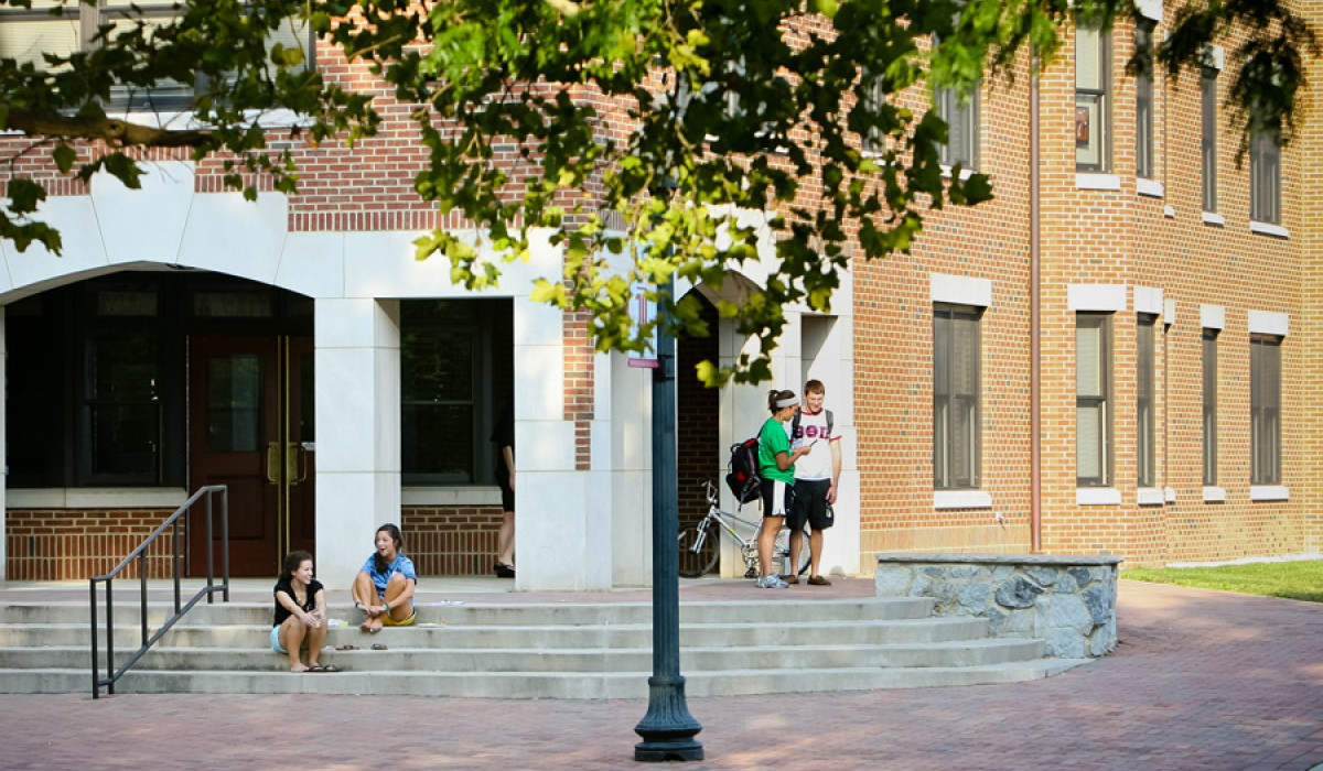 Students outside of the building - two sitting on steps
