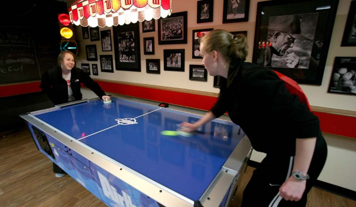 Students playing air hockey in game room